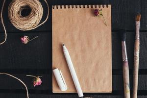 maquete de papel em branco com pincéis de artista na mesa de madeira foto