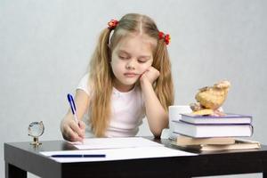 a criança joga lições na mesa foto