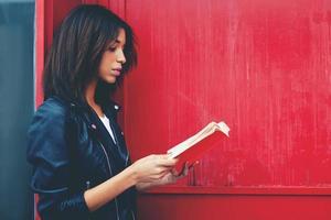 mulher afro-americana ler literatura em pé ao ar livre