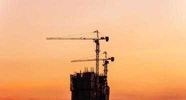 guindastes de construção à noite. silhueta de tiro foto