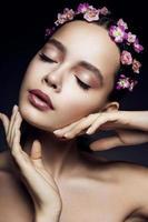 uma garota posando com flores cor de rosa no cabelo