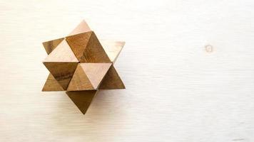 quebra-cabeça de madeira cubo pontudo na superfície de madeira foto