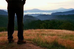 pernas de mulher alpinista em botas de turista ficar no pico da colina foto