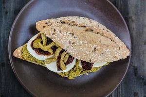 sanduíche gourmet com molho pesto e azeitonas foto