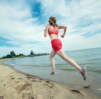 jovem correndo na praia de areia do verão ensolarado. exercite-se foto