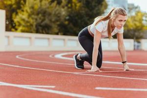 mulher de esportes em posição de estrela para correr foto