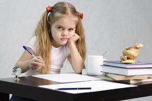 garota fazendo lições na mesa foto