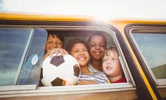 alunos bonitos sorrindo para a câmera no ônibus escolar