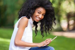 garota negra de tenage usando um tablet tátil foto