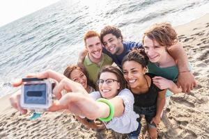 grupo multirracial de amigos tomando selfie na praia