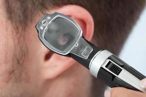 médico verificando a orelha do paciente foto