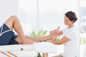 fisioterapeuta fazendo massagem nas pernas foto