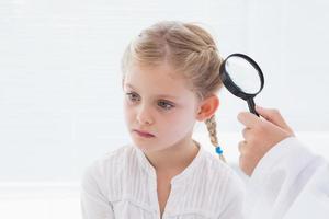 médico examinar paciente com lupa foto