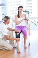médico examinando seu joelho pacientes foto