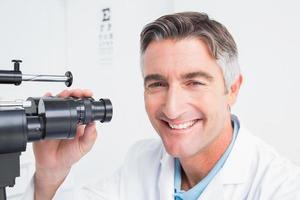 oculista feliz usando lâmpada de fenda na clínica foto