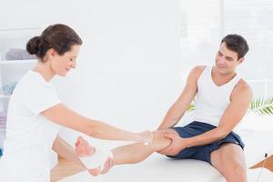 médico enfaixando o tornozelo do paciente foto