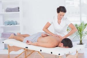 fisioterapeuta fazendo massagem nas costas foto