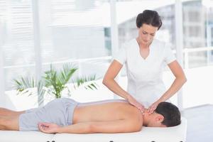 fisioterapeuta fazendo massagem no pescoço para seu paciente foto