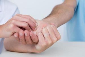 médico fazendo massagem nas mãos foto