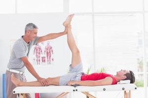 fisioterapeuta fazendo perna esticando para seu paciente foto