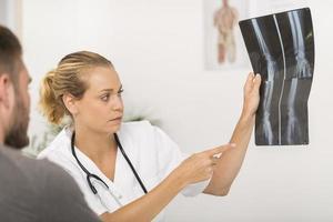 cirurgião mostrando raio-x para paciente no consultório médico foto
