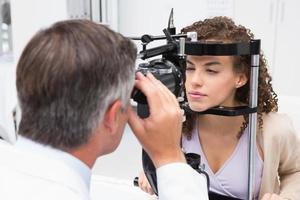 mulher fazendo exame oftalmológico com optometrista foto