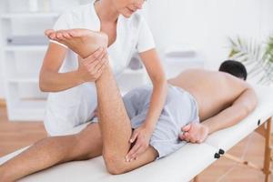 fisioterapeuta fazendo massagem nas pernas para seu paciente foto