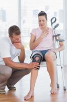 médico examinando o joelho do paciente foto