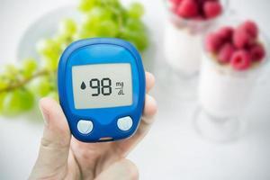 diabetes fazendo teste de nível de glicose. frutas no fundo foto