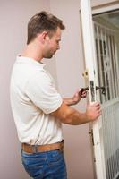trabalhador manual testando a maçaneta da porta foto
