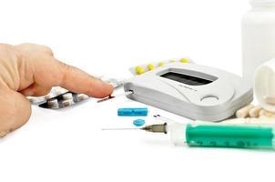 glicosímetro com uma mão, medicamentos e uma seringa foto