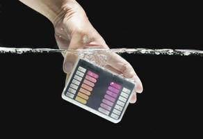 mergulhando o kit de teste de água na água foto