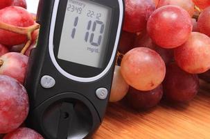 medidor de glicose e uvas naturais frescas na tábua foto