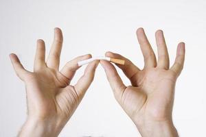 mãos esmagando cigarro foto