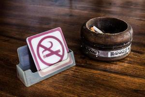 placa de proibido fumar e cinzeiro de madeira vintage na mesa foto