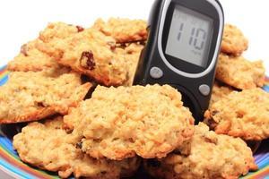 biscoitos glicosímetro e aveia no fundo branco foto