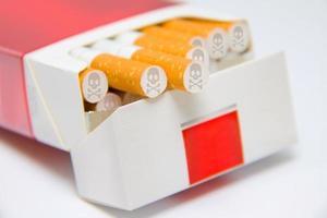 cigarros na caixa marcada com sinal de caveira e ossos foto