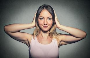 mulher feliz, cobrindo com as mãos os ouvidos foto