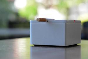 cinzeiro branco e cigarro em cima da mesa foto