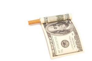 cigarro e nota de cem dólares em fundo branco foto