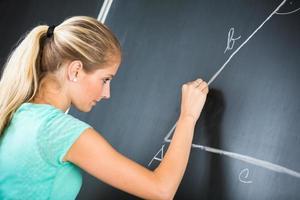 professor muito jovem, escrevendo no quadro-negro
