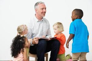 professor de pré escola lendo história para crianças