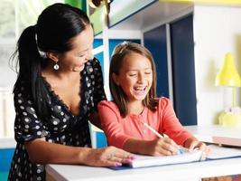 mãe ajudando filha feliz com lição de casa
