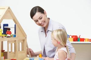professor de pré-escola e aluno brincando com casa de madeira foto