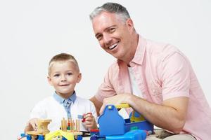 professor e aluno de pré escola brincando com ferramentas de madeira
