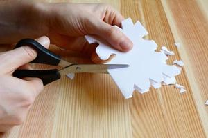 usando uma tesoura para cortar uma forma de floco de neve de papel foto