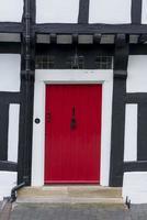 porta da frente vermelha em uma casa de madeira emoldurada tudor