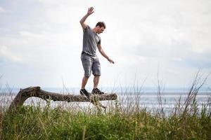 adulto jovem, equilibrando-se em uma árvore em férias foto