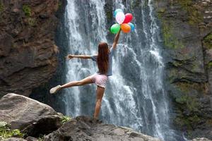 jovem mulher com balões no fundo da cachoeira