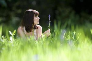 jovem no campo com flores silvestres, vista lateral foto